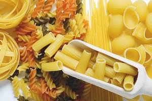 Wooden spoon with macaroni over various types of pasta.