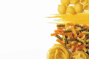 Close-up of various types of pasta on white background. Copy space.