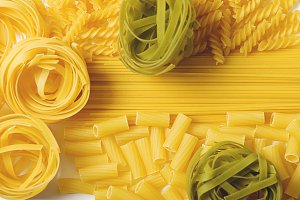 Background of spaghettis and macaroni on white background. Italian pasta. Horizontal shoot. Copy space.