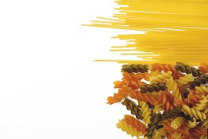Spaghetti and curly macaroni on white background. Copy space.