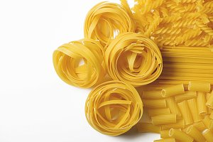 Background of close-up spaghettis and macaroni on white background. Italian pasta. Horizontal shoot. Copy space.