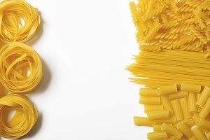 Background of various types of pasta with white space in the middle. Copy space. Horizontal shoot.