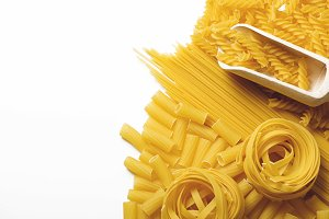 Background of spaghetti and macaroni next to a wooden spoon. Copy space. Horizontal shoot.
