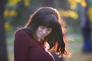 Portrait of Pregnant woman standing at autumn park and looking to her belly