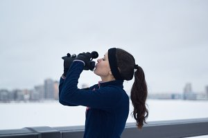 Sport female drinks water on jogging outside at cloudy winter day
