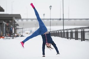 Fitness girl have acrobatic work out fitness at snow winter promenade