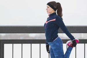 Female runner doing flexibility exercise for legs before run at snow winter promenade, vertical