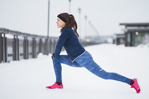 Young woman runner doing flexibility exercise for legs before run at snow winter promenade,