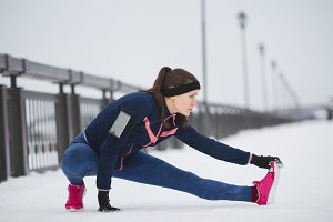 Woman runner stretching legs before run. Young athlete woman working out. Fitness concept.
