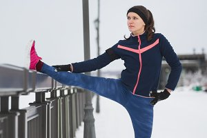 Fitness girl in pink sneakers doing stretching outside at cloudy winter day