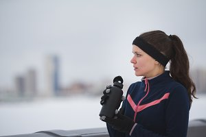 Young woman jogging outside cloudy winter day - drink water