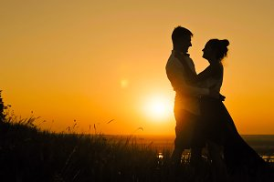 Young loving couple -  man and beautiful girl stands on high hill at sunset  have hugs  kiss, silhouette