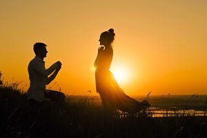 Romantic Silhouette of Man Getting Down on his Knee and Proposing to Woman  high hill - Couple Gets Engaged at Sunset -  Putting Ring  Girl's Finger, slider shot