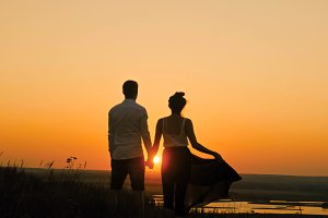 Young loving couple - brave man and beautiful girl at dusk silhouette, looking to sun