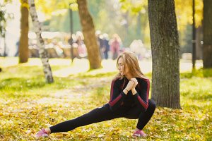 Sexy Attractive female blonde bikini-fitness model stretching in the autumn park on ground covered yellow leaves - legs flexibility - the right side