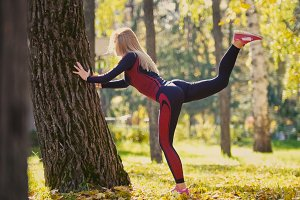 Fitness woman strength training doing workout at sunny autumn park. Fit caucasian sporty girl exercising her body near tree - lifts legs alternately, slow-motion