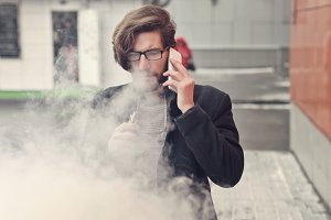 Man with e-cigarette and cell phone