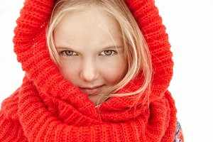 Winter portrait of pretty charming little girl with blonde hair and fair skin posing outdoors wearing red knitted wrap scarf, looking and smiling at camera, freezing, playing with other kids in prak