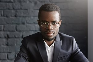 Close-up shot of handsome young dark-skinned entrepreneur in spectacles and formal wear having serious and thoughtful facial expression while sitting isolated against black brick wall background