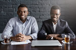 Portrait of two cheerful African-American businessmen or business partners sitting at desk with laptop computer and papers, ready to start meeting, both looking at camera with happy expression
