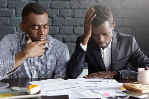 People, business and failure. Two tired and depressed African-American businessmen doing paperwork, reviewing accounts, working on financial report together, having stressed and frustrated looks