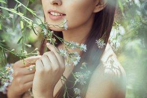 Beautiful young woman portrait in flower field