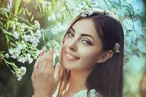 Beautiful young woman portrait in flower field