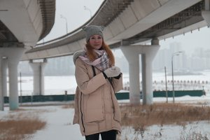 Young pretty woman stands under large bridge, winter city