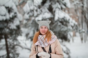 Pretty young girl with red hair standing in winter park near snow pines