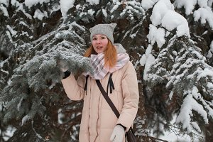 Pretty young girl with red hair standing near snow pines in winter park