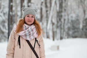 Pretty young girl with red hair in hat standing near snow pines in winter park