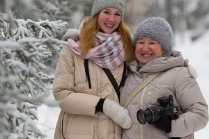 Young woman and adult female in winter park - standing near snow-covered pines