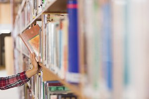 Pretty student taking book out of shelf