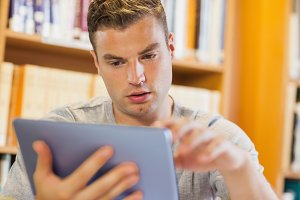 Attractive serious student using tablet
