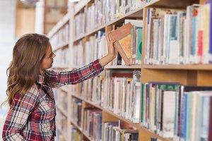 Pretty student placing book in shelf
