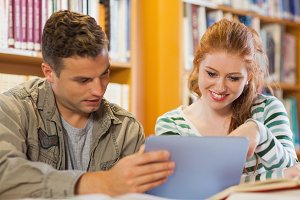 Two cheerful students studying together using tablet