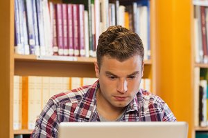 Handsome focused student using laptop