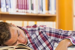 Exhausted handsome student resting head on piles of books