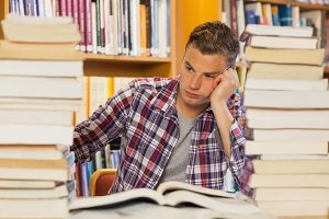 Frustrated handsome student studying between piles of books