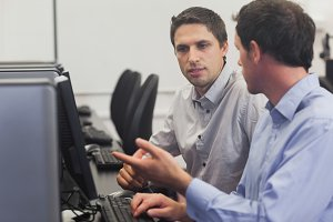 Two attractive men talking in computer class