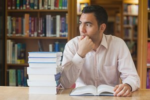 Attractive man sitting in library in front of an opened book
