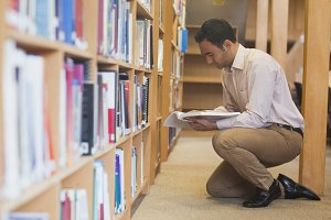 Attractive casual man reading a book in library
