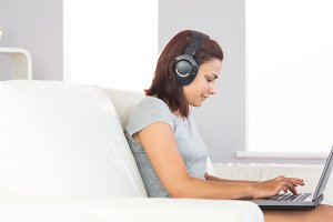 Cute casual woman witting on couch using her notebook and listening to music