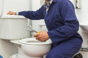 Good looking plumber repairing toilet