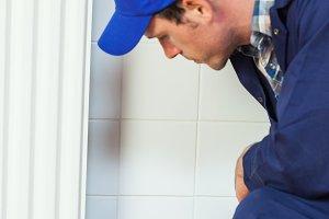Serious handyman in blue coveralls repairing a radiator