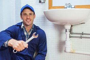 Happy plumber holding wrench sitting next to sink