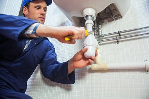 Frowning plumber repairing sink
