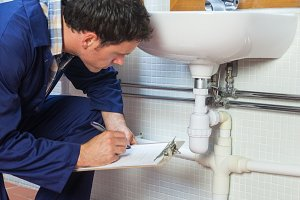 Handsome plumber inspecting sink holding clipboard
