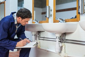 Handsome plumber looking at sink holding clipboard