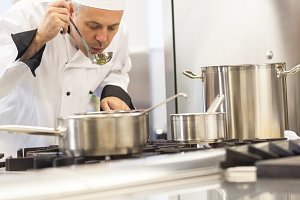 Concentrating head chef tasting food from ladle